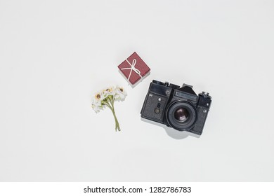 Minimalistic flat lay composition with retro camera, vinous gift box and spring field flower on white background. Trendy flat lay mockup for bloggers, designers, photographers, etc.