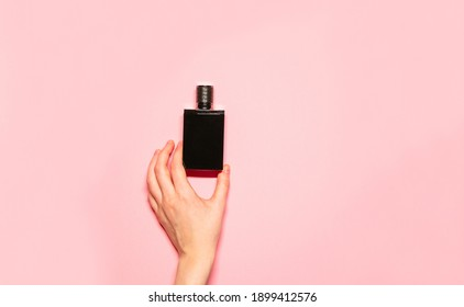 Minimalistic flat lay photo of a woman's hand holding fragrant perfume in a stylish black glass bottle on a pastel pink background.