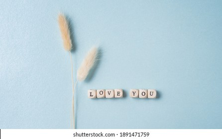 minimalistic flat lay with white dried flowers and cubes with the word love you on blue background. Concept of Valentine's Day, Mother's Day, wedding day. Top view and copy space