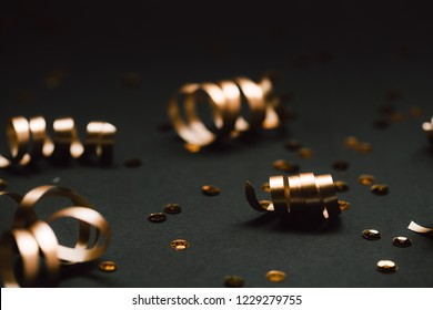 Minimalistic golden decor on black background. Selective focus. Festive concept.