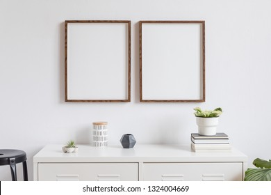 Minimalistic home decor of interior with two brown wooden mock up photo frames on the white shelf with books, beautiful plant in stylish pot, box and home accessories. White walls. Mockup concept.
