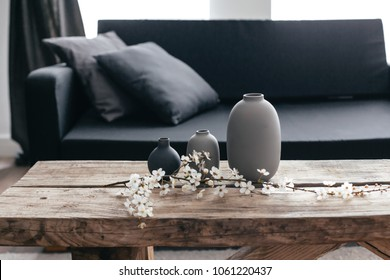 Minimalistic home decor on rustic coffee table over black sofa with cushions. Grey vases and spring flowers on wooden bench in small dark room interior. Scandinavian home style.