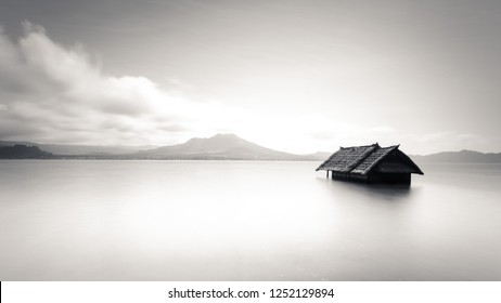 Minimalistic image of abandoned house floating on water. Clean and simple image of alone house in middle of nowhere. Simplicity photo of lonely isolated house. Peaceful serene image of lost building.