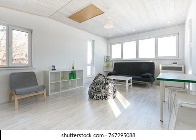 minimalistic living room interior, photo in cottage with wooden white celling, white painted walls, laminate floor.