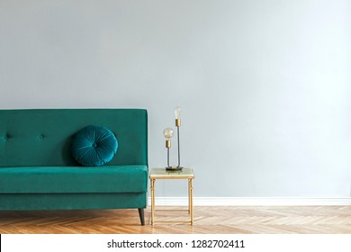 Minimalistic and luxury grey home interior with green velvet design sofa, gold coffe table with table lamp. Copy space for inscription, mock up poster. Empty wall. Brown wooden parquet.