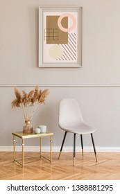 Minimalistic and luxury living room of apartment interior with elegant marble table, gray velvet chair and chic accessories. Mock up paintings frame on the molding gray wall. Stylish home decor.