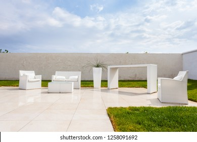 a minimalistic outdoor living with white furnitures