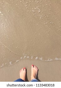 Minimalistic photo of a woman's feet, standing on the shore of a sandy beach