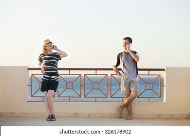 Minimalistic portrait of young happy smiling couple, man and woman holding cellphones, talking on mobile phones, standing in relaxed poses on sunny summer terrace with sea scenery