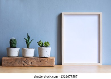 Minimalistic room interior with mock up photo frame on the brown wooden table with beautiful cacti in design hipster white pot. Grey walls. Stylish and floral concept of mock up poster frame.