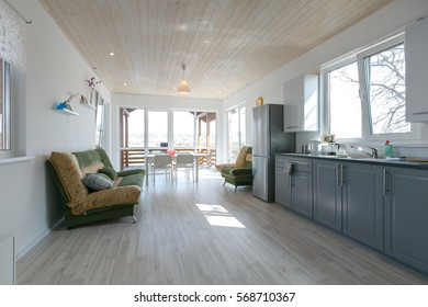 Minimalistic scandinavian grey kitchen with grey fridge. White wooden floor and ceiling. White painted walls.