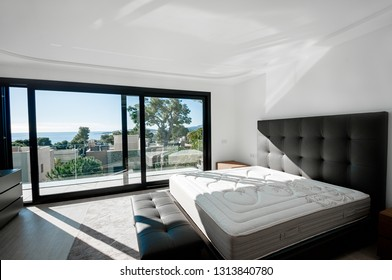 Minimalistic style bedroom in brown and beige tones with new mattress.