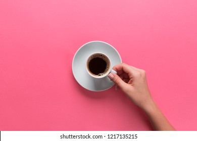Minimalistic style woman hand holding a cup of coffee on pink background. Flat lay, top view.