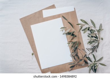 Minimalistic wedding mockup with a blank invitation card and a fresh olive twig on a white soft textile linen background, flat lay, top view