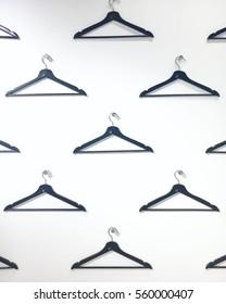 Minimalistic Well-Organized White Wall of Empty Coat Hangers