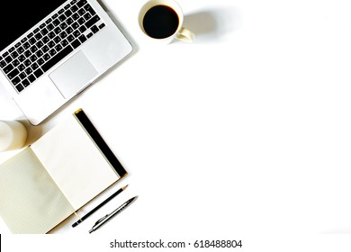 Minimalistic work place. White office desk table with laptop, roses, vintage white tray, notebook, coffee cup, pen and pencil. Top view with copy space, flat lay