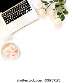 Minimalistic workplace with laptop keyboard and roses in flat lay style. White background, top view