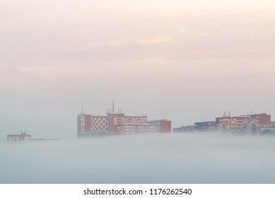 Minimalistist Photography. Morning fog under buildings in the city Zlin, Czech Republic, Europe, during a colorful sunrise. Only top of buildings in a hill are visible