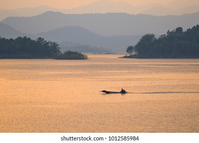 minimallist image of a fishing boat in orange light reflecting on the surface. With a mountainous background .soft and select focus.