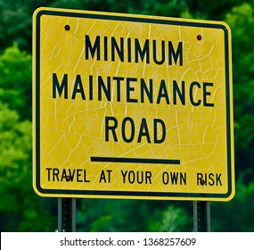 A minimum maintenance sign appears befor bright green leaves.