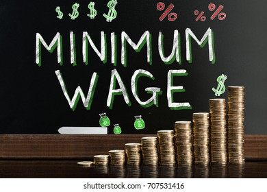 Minimum Wage At Blackboard Behind Stacked Coins
