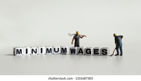'MINIMUM WAGES' word in white cube. Miniature people.