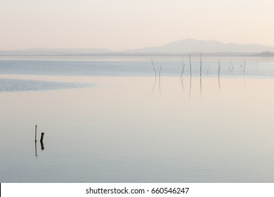 Mininalist view of a lake, with some wooden poles in the foreground and soft colors