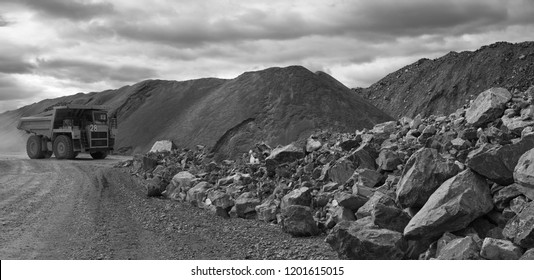 Mining dump truck on the background of dumps of stone ore and large rock debris, black and white panorama.