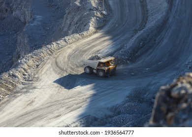 Mining dump truck raises up the road of rock extracted in shale quarry, view from above.