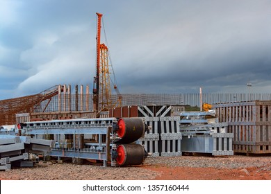 Mining equipment spare parts are stored in an open-air area in front of a warehouse under construction. Kamsar, Guinea.