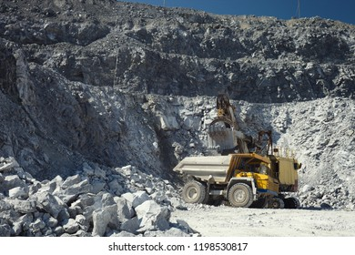 Mining excavator and heavy mining truck in a quarry for the extraction of limestone on the background of rocky terrain in sunny weather, close-up.