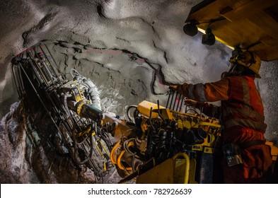 Mining machine arm drilling minerals