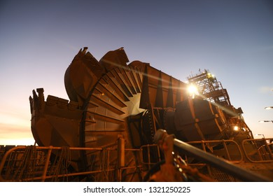 Mining reclaimer wheel bucket heavy machinery early morning sunrise at the back ground construction copper mine site New South Wall, Sydney, Austrian