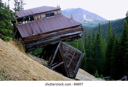 Mining shack balancing on remains of another bulding after a landslide on Mt. Princeton, Colorado.