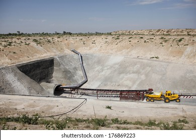 A mining vehicle is parked just outside on the entrance of an inclined diamond mine shaft in the desert