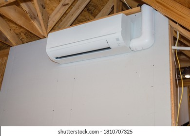 Mini-split ductless air conditioning unit installed in unfinished room
