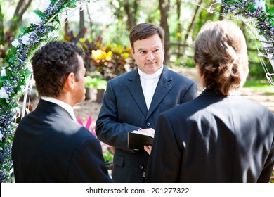 Minister performing marriage ceremony for two grooms at a gay wedding.
