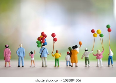 Miniture family with balloon  standing and looking forward use as happy background.