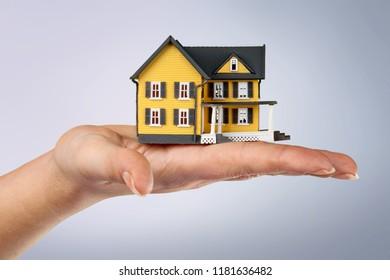 Miniture house model human hand displaying