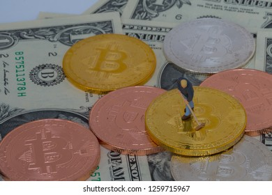 miniture people with crypto currency gold silver bronzen bitcoin with dollar banknotes background