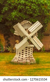 Miniture wooden windmill with peeling white paint nestled in the grass in front of a brick wall