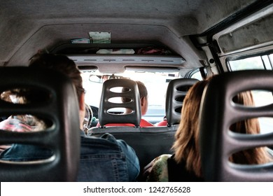 Minivan passengers share a ride: Group of people traveling in a minivan shot from backseat