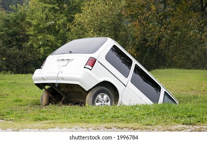 Minivan sinking into the ground.  Halfway submerged with the front end completely underground.