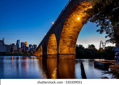 MINNEAPOLIS - JUL 27: A view of the beautiful stone arch bridge of Minneapolis, MN, USA at dusk, showing part of the city skyline on Jul 27, 2014 in Minneapolis, USA