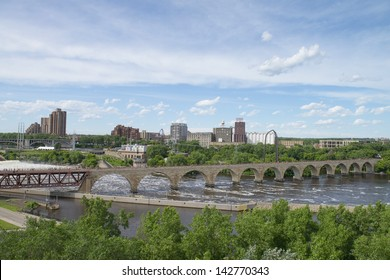 MINNEAPOLIS - JUN 16: Downtown Minneapolis, MN at noon time on Jun 16, 2013 as seen the Stone Arch bridge. It's a former railroad bridge crossing the Mississippi River at Saint Anthony Falls.