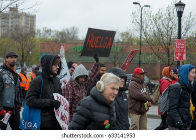 """MINNEAPOLIS - MAY 1, 2017: A marcher holds up a sigh reading """"huelga"""" (Spanish for """"strike"""") during an International Worker's Day march in Minneapolis on May 1, 2017."""