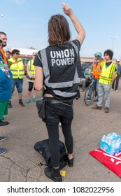 """MINNEAPOLIS - May 1, 2018: A trans rights activist, wearing a vest reading """"union power,"""" waits for the International Workers' Day March."""