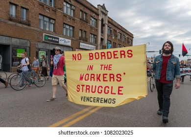 MINNEAPOLIS - May 1, 2018: Two individuals march with a large sign in the International Workers' Day March, hosted by a number of community organizations and labor unions.