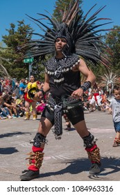MINNEAPOLIS - May 6, 2018: A man in traditional Aztec dress dances in Minneapolis's yearly May Day parade, organized by In the Heart of the Beast Puppet and Mask Theatre.