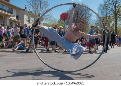 MINNEAPOLIS - May 6, 2018: A man spins in a large metal hoop during Minneapolis yearly May Day parade.